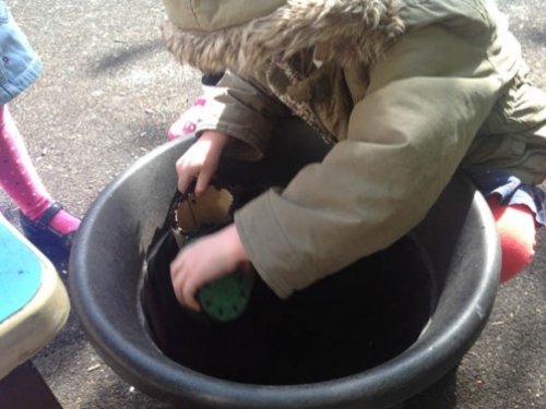 Lucy putting compost into the new bamboo pots